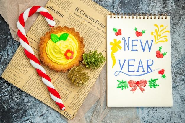 Biscotto vista dall'alto con ornamenti natalizi su giornale e anno nuovo scritto su taccuino su sfondo scuro