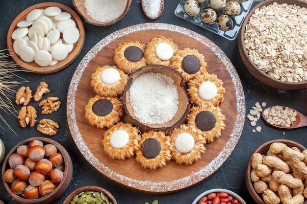 테이블에 귀리 견과류와 사탕이 있는 비올 그릇에 나무 판자에 초콜릿과 코코넛 가루를 넣은 탑 뷰 비스킷