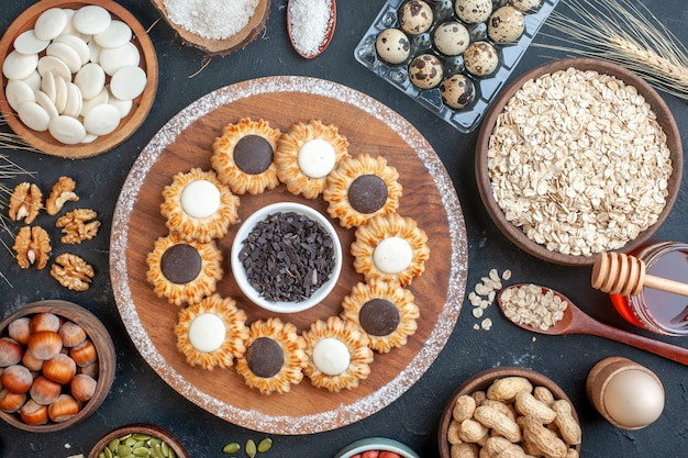 Top view biscuits with chocolate and dark chocolate on wood board bowls with nuts oats candies quail eggs in viol honey jar egg in eggcup on table