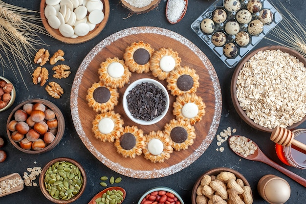 Top view biscuits with chocolate and dark chocolate on wood board bowls with nuts oats candies quail eggs in viol honey jar on table