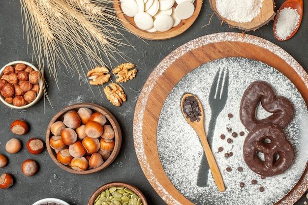 접시에 설탕 나무 숟가락을 입힌 초콜릿 포크 인쇄물이 있는 평면도 비스킷 화이트 초콜릿 라운드 테이블에 있는 그릇에 코코넛 가루 헤이즐넛