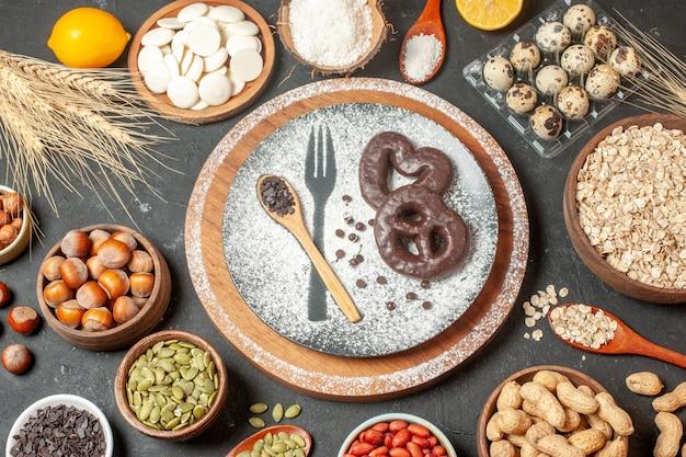접시에 설탕 나무 숟가락을 입힌 초콜릿 포크 인쇄물이 있는 상위 뷰 비스킷 화이트 초콜릿 라운드 코코넛 가루 귀리 그릇에 메추리알