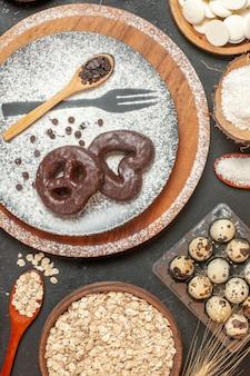 접시에 설탕 나무 숟가락을 입힌 초콜릿 포크 인쇄물이 있는 상위 뷰 비스킷 화이트 초콜릿 라운드 그릇에 코코넛 가루 귀리 테이블에 메추라기 알