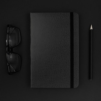 Top view of black agenda and glasses