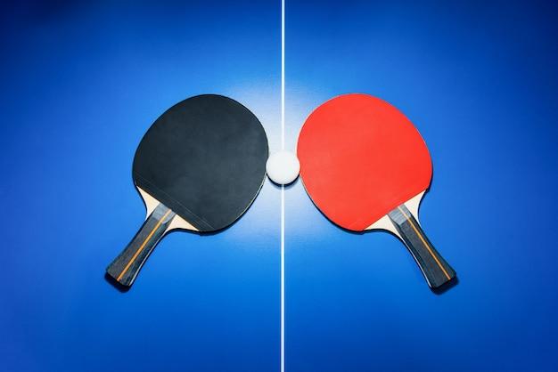 밝은 스포트라이트가 있는 파란색 탁구대 위에 있는 검은색과 빨간색 탁구 라켓과 흰색 탁구공, 탁구 패 2개는 실내 운동을 위한 스포츠 경기 장비입니다.