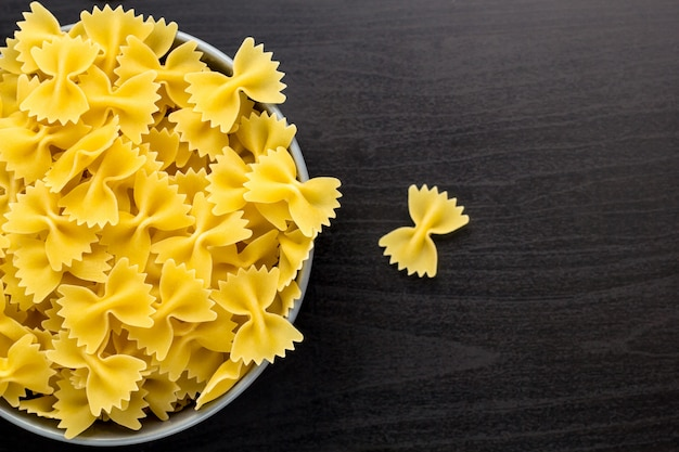 Top view of black background with italian raw farfalle or pasta in bowl