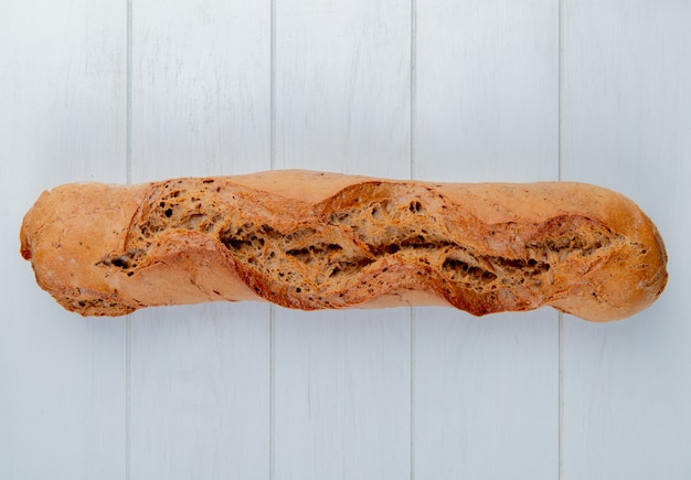 Top view of black baguette on left side and wooden background with copy space