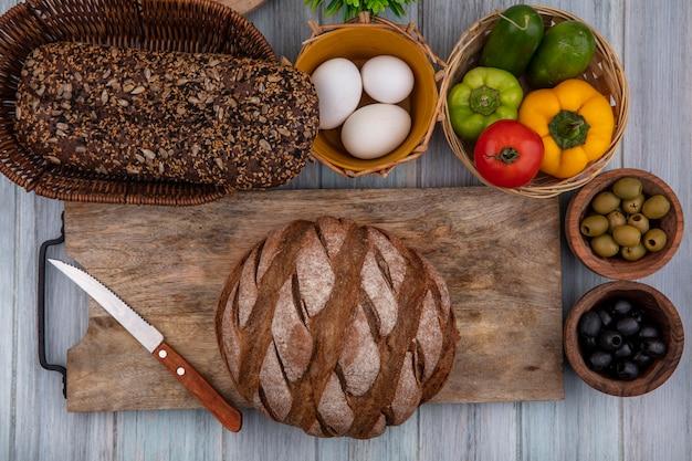 Vista dall'alto pane nero su un supporto con uova di gallina pomodoro peperoni cetrioli e olive