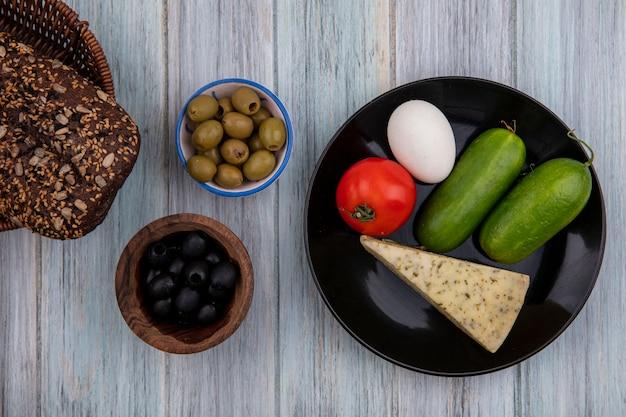 灰色の背景に黒と緑のオリーブとプレートにチーズきゅうりトマトと卵の上面図黒パン