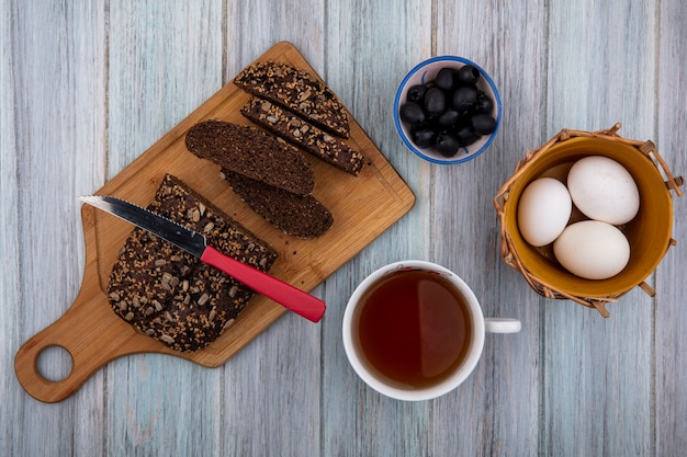 Top view black bread with knife on board with cup of tea  chicken eggs and olives on gray background