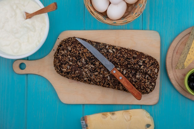 Vista dall'alto pane nero con coltello sul tagliere e uova di gallina con yogurt in una ciotola su sfondo turchese