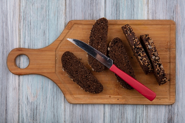 Top view black bread with knife on cutting board  on gray background