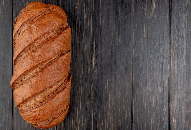 Top view of black bread on wooden background with copy space