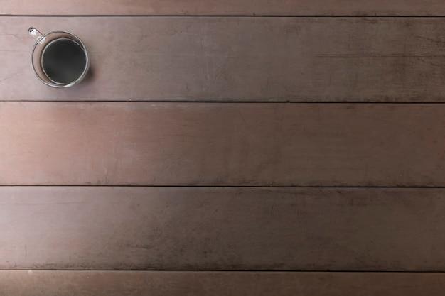 古い木製のテーブルの上から見るブラックコーヒーカップ。コピースペース付きハンドルカップでコーヒー。煙でホットブラックコーヒー。