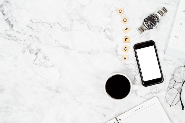 Top view of black coffee cup with eyeglasses and watch on desk with copy space