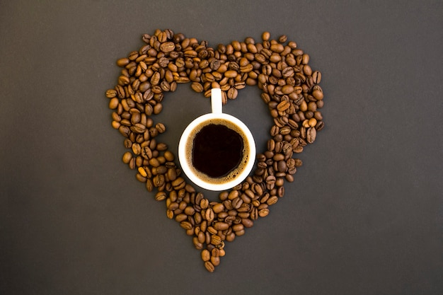 Top view of black coffee in the white cup and heart made of coffee beans on the dark background