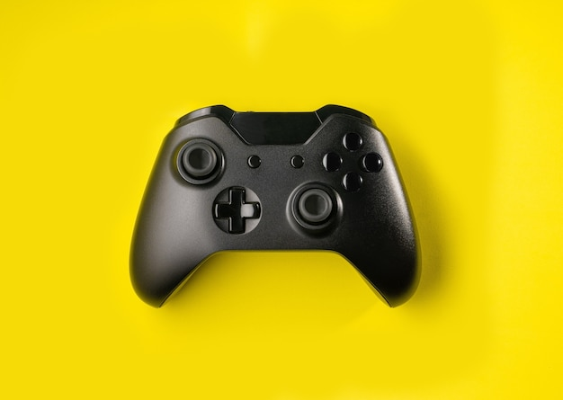 Top view black controller on yellow space