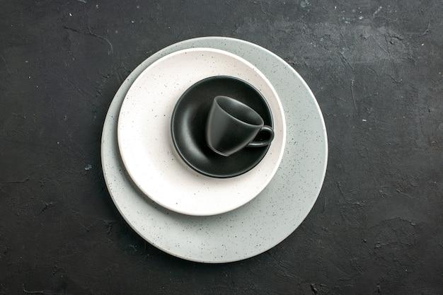 Вид сверху черная чашка блюдце белая тарелка на серой тарелке на темной поверхности свободное пространство