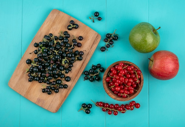 Top view black currant on a board with red currants in a bowl and apples on a light blue background
