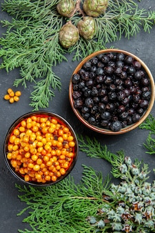 Top view black currant sea buckthorn in bowls pine branches on dark surface
