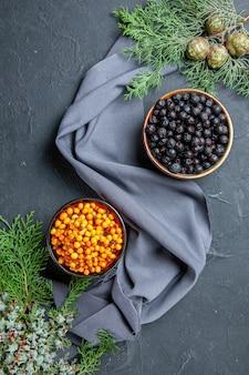 Вид сверху черная смородина облепиха в мисках сосновые ветки фиолетовый платок на темной поверхности