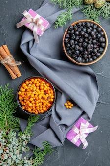 Вид сверху черная смородина облепиха в мисках сосновые ветки фиолетовый платок маленькие подарки на темной поверхности