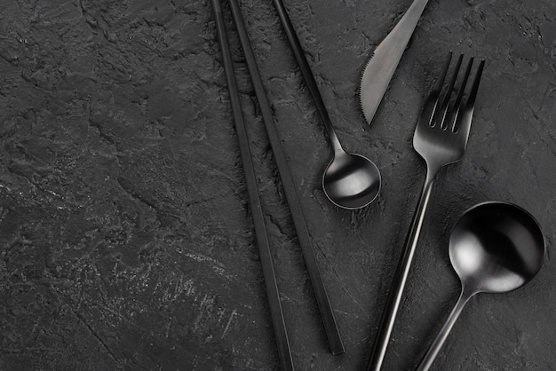 Top view of black cutlery on slate