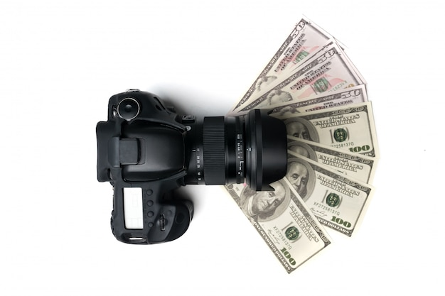 Top view of a black digital camera on banknotes with white background.