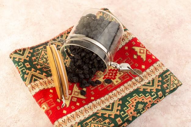 Una vista dall'alto frutta secca nera all'interno del barattolo rotondo su un tappeto dal design colorato sul rosa