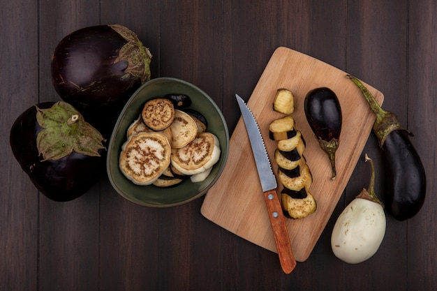 Top view black eggplant with wedges in a bowl and on a cutting board with a knife on a wooden background