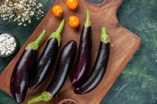 Vista dall'alto melanzane nere sul tagliere superficie scura colore alimentare cena pasto insalata fresca verdura