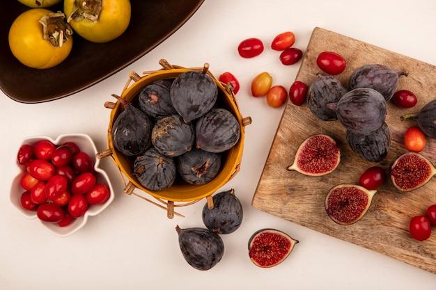 Vista dall'alto di fichi neri su un secchio con ciliegie di corniola su una ciotola con fichi neri e ciliegie di corniola isolato su una tavola da cucina in legno su un muro bianco