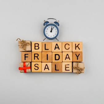 Top view of black friday cubes and clock on plain background