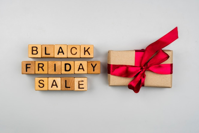 Top view of black friday cubes and gift on plain background
