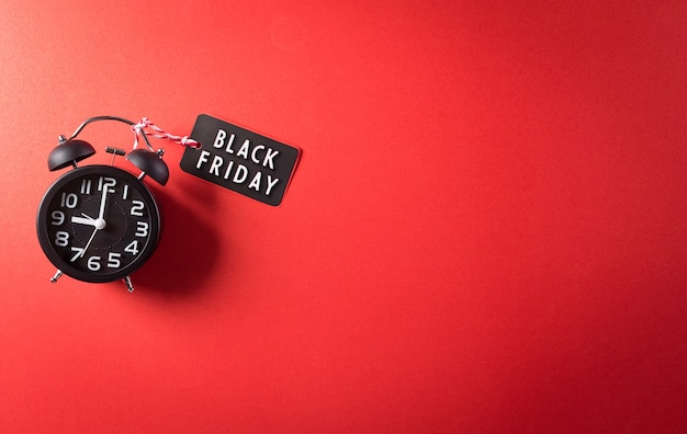 Top view of black friday sale text with alarm clock on red background
