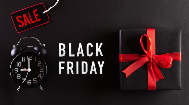 Top view of black friday sale text with black gift box and alarm clock
