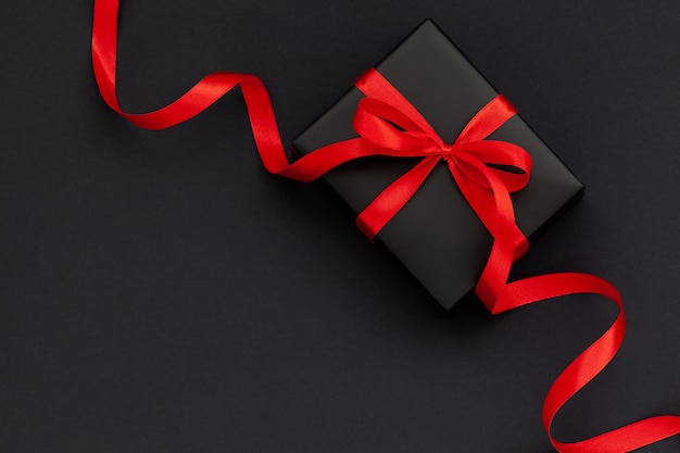 Top view of black gift box with red ribbon on black background with copy space for text