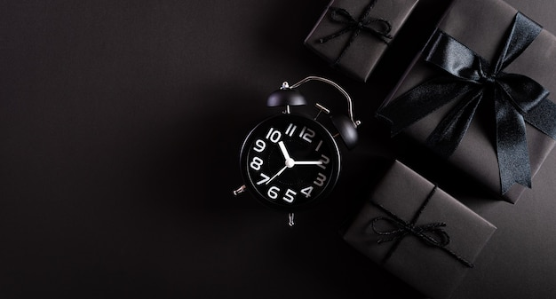 Top view of black gift boxes with alarm clock