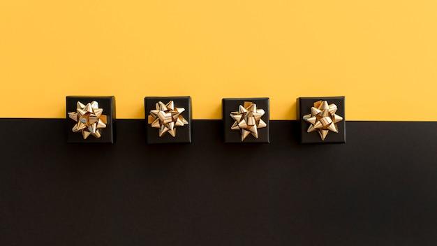 Вид сверху черные подарочные коробки с золотыми лентами