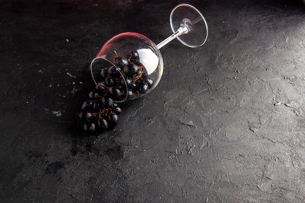 Vista dall'alto uva nera in un bicchiere di vino capovolto su sfondo scuro