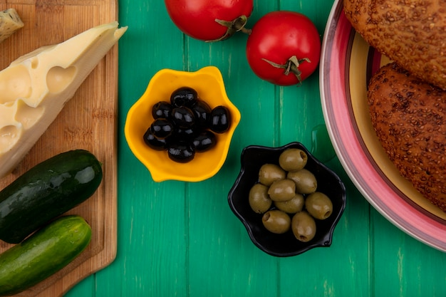 Top view of black and green olives on a bowl with cucumbers and cheese on a wooden kitchen board with soft and sesame patties on a plate on a green wooden background