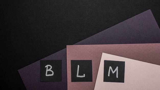 Vista dall'alto delle carte di materia viva nera con lettere su carta multicolore