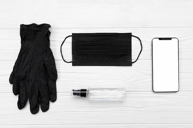 Вид сверху черная медицинская маска, перчатки и пустой телефон