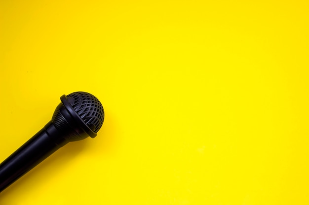 Top view black microphone over yellow background. pianist musician, pianist concept. copy space.
