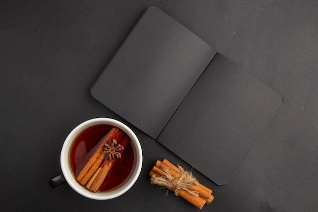 Вид сверху черный блокнот чашка чая, приправленная корицей и анисом, палочки корицы, перевязанные веревкой на темном столе