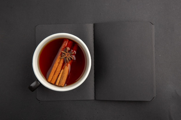 Top view black notepad cup of tea flavored by cinnamon and anise on dark table