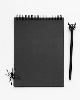 Вид сверху черный блокнот с пауком сверху