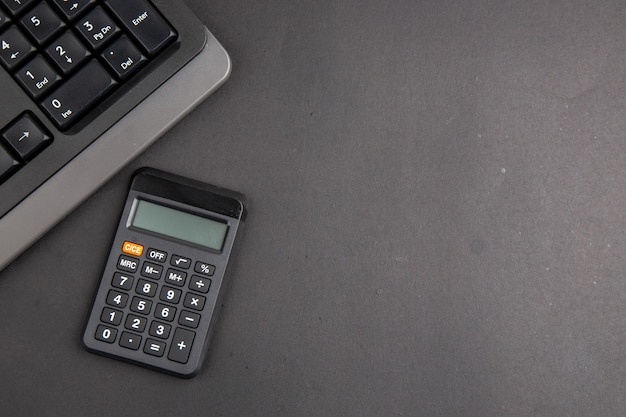 Top view black office stuffs keyboard calculator on dark table copy space Free Photo