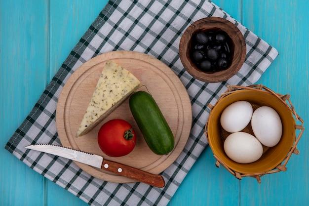 ターコイズブルーの背景に市松模様のタオルでチーズキュウリトマトと鶏卵と上面図ブラックオリーブ