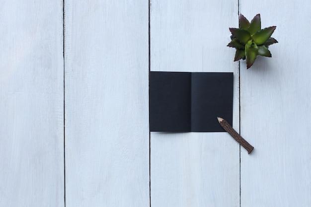 흰색 나무 바닥에 상위 뷰 검은 종이, 연필, 화분 및 복사 공간이 있습니다.